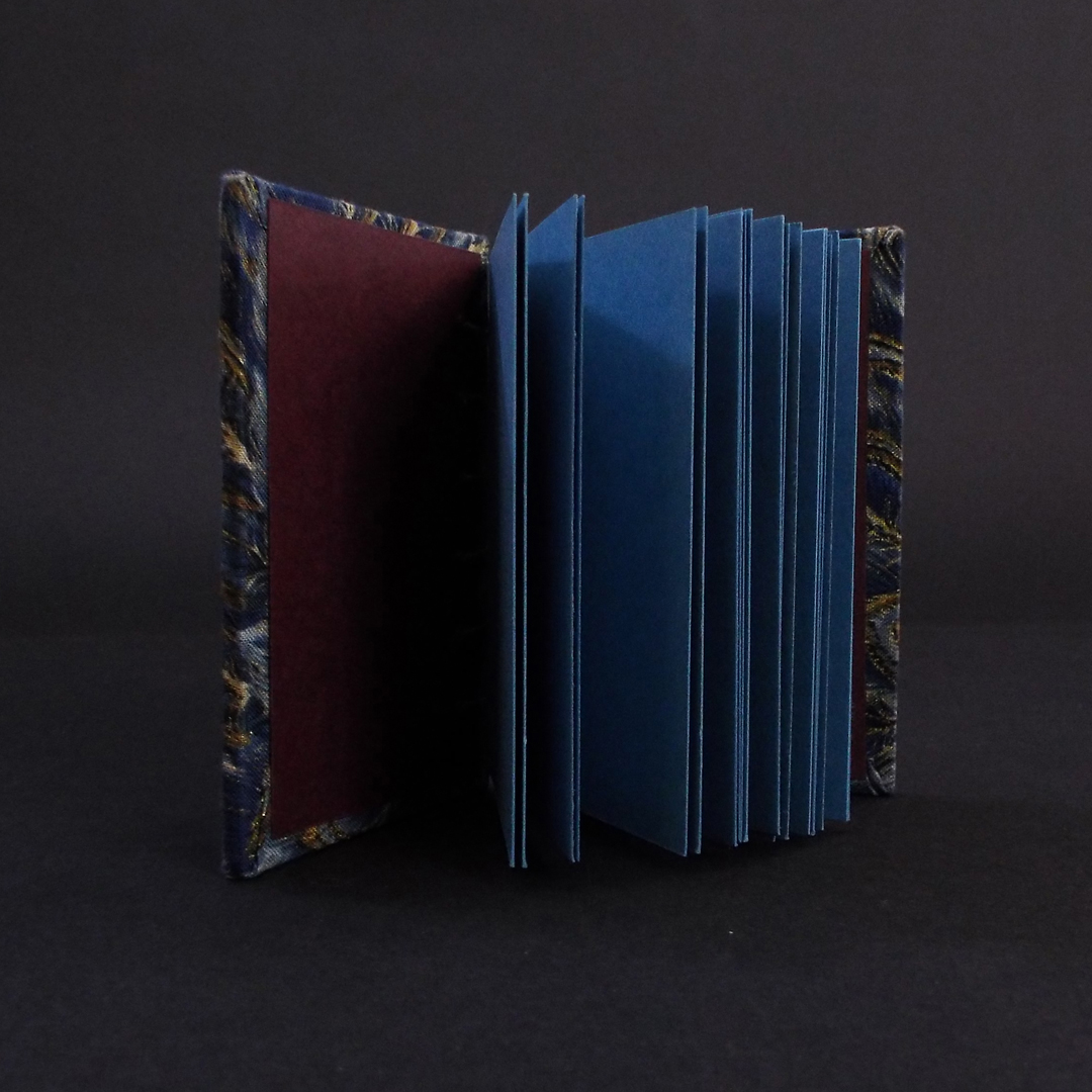 Blue peacock mini coptic bound book inside showing the blue text block and burgundy end pages