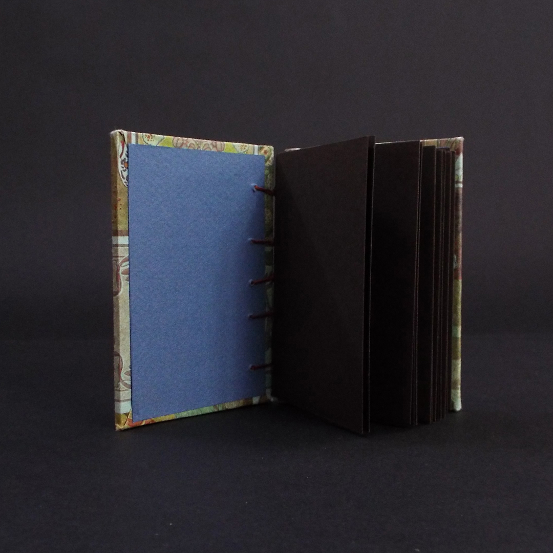 Art nouveau floral coptic bound journal inside showing brown text block pages and navy blue end pages