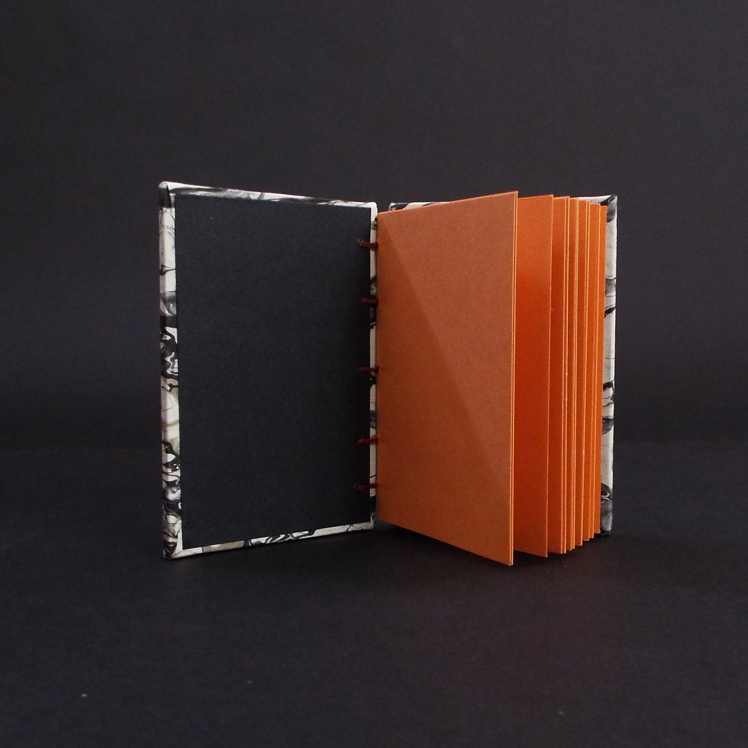 Black marbled mini coptic bound book inside showing orange text block and black end pages