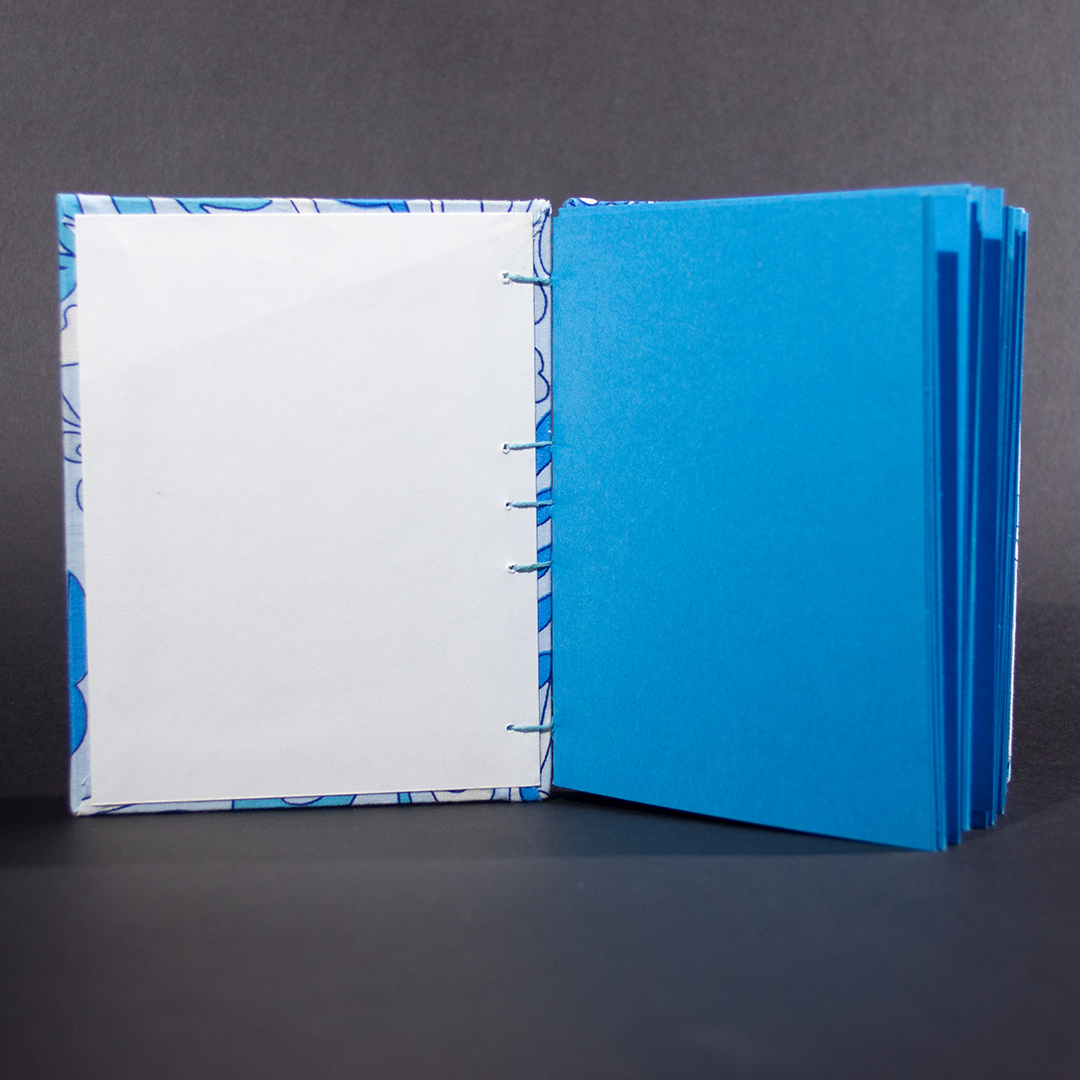 View of the end pages and the blue card stock pages of blue floral octavo Coptic bound journal