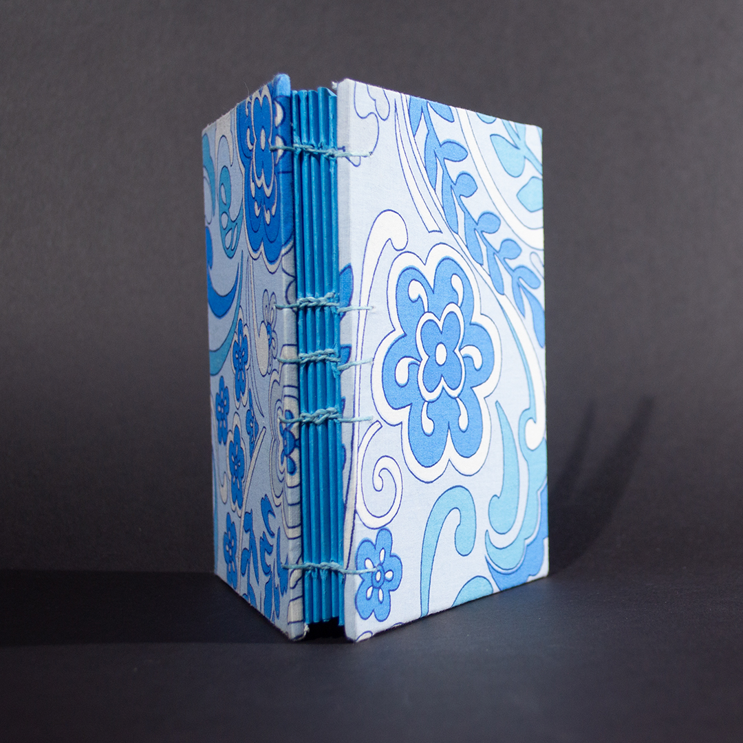 The spine of blue floral octavo Coptic bound journal