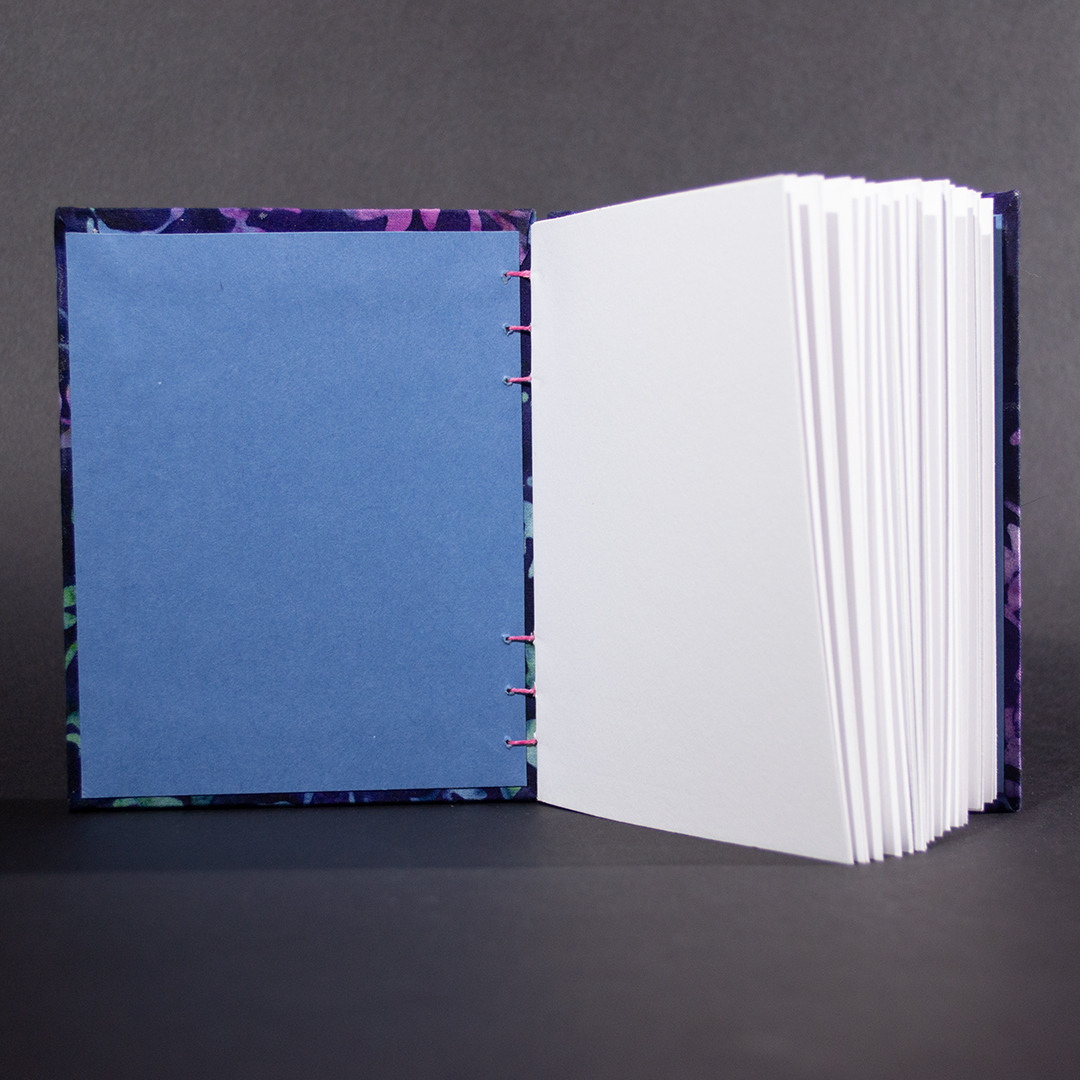 Blue Batik Vines octavo Coptic bound journal showing blue end pages and white text pages.