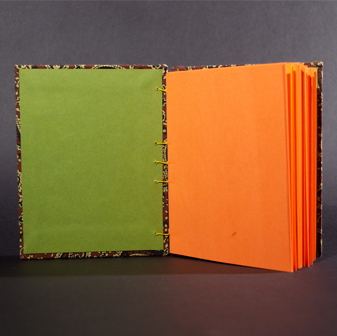 Brown paisley octavo Coptic bound journal inside shot of olive end pages and orange card stock text pages.