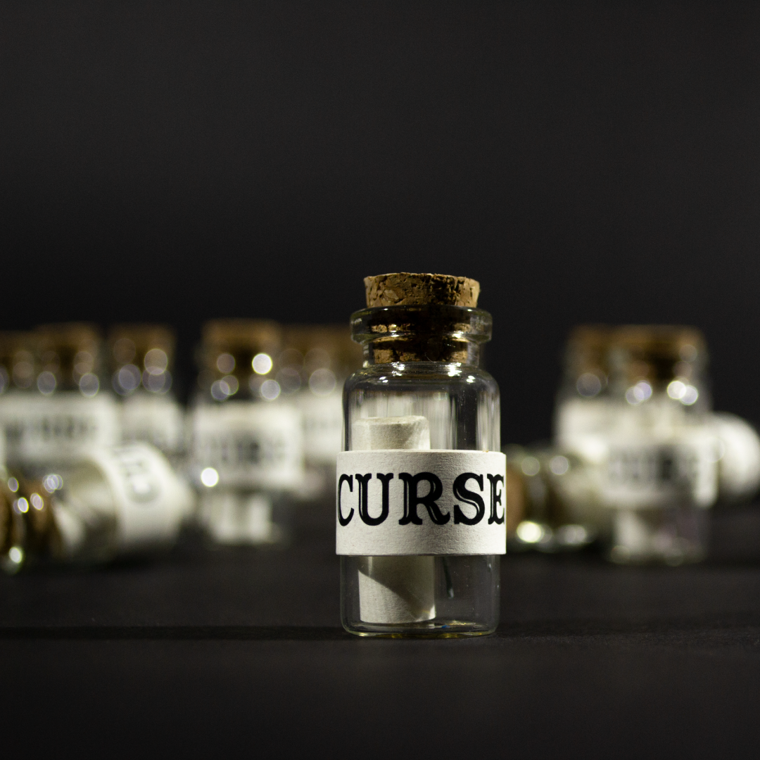 Curses product shot. A photo of a small glass bottle with a scroll inside. The outside is wrapped in paper and labelled curse.