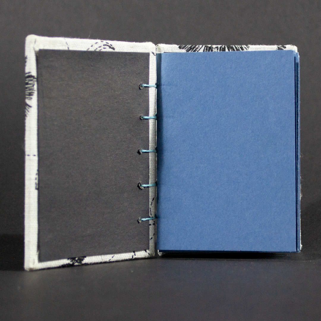 Inside shot of black and white floral mini Coptic book showing blue cardstock pages and black end pages