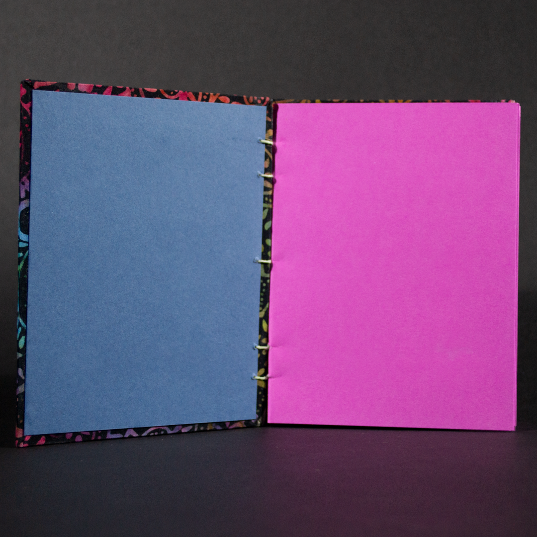 Insides of rainbow batik flowers octavo Coptic book showing the bright pink cardstock inside pages and blue end pages