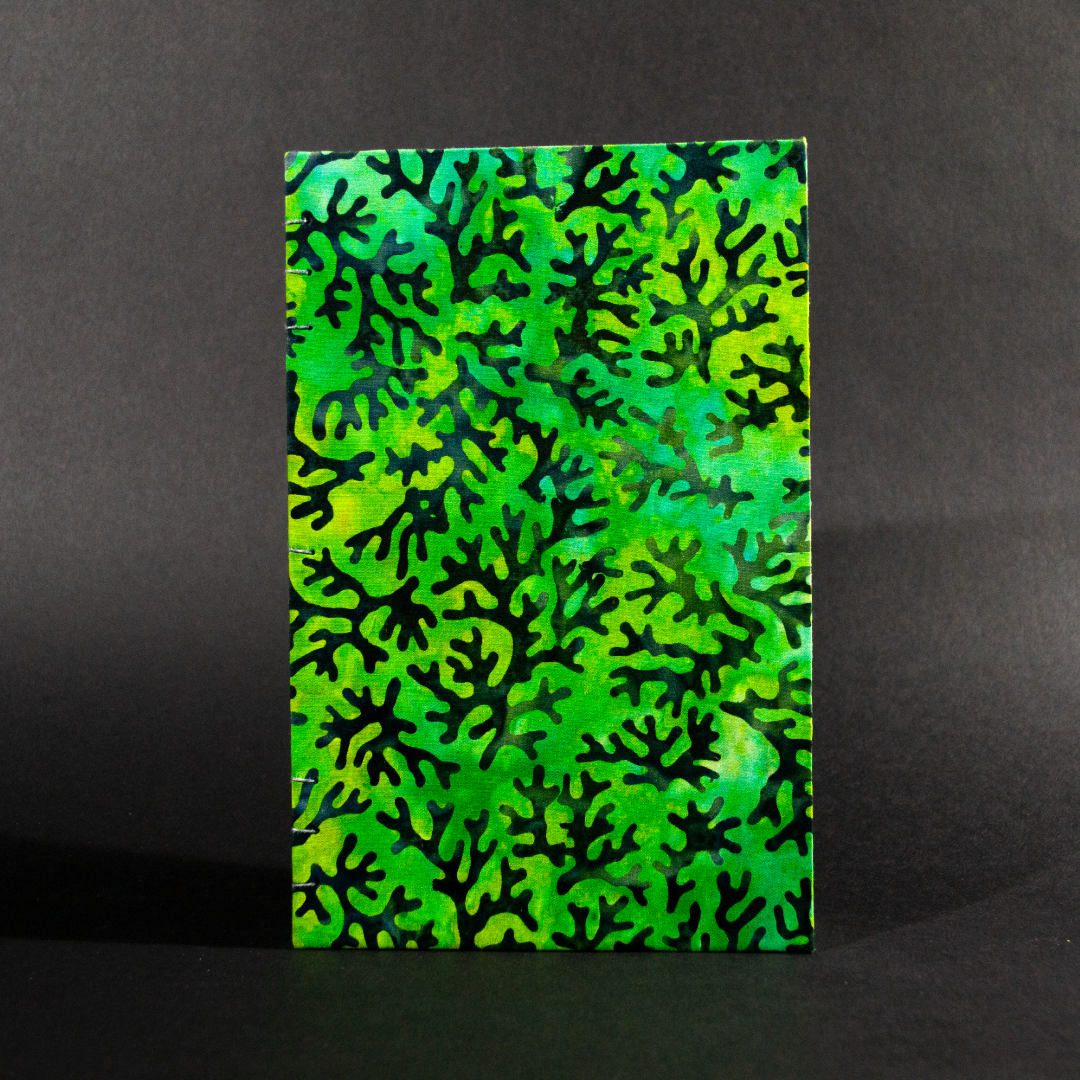 The front cover of blue coral batik quarto Coptic book with blue coral designs on a blue and green background.