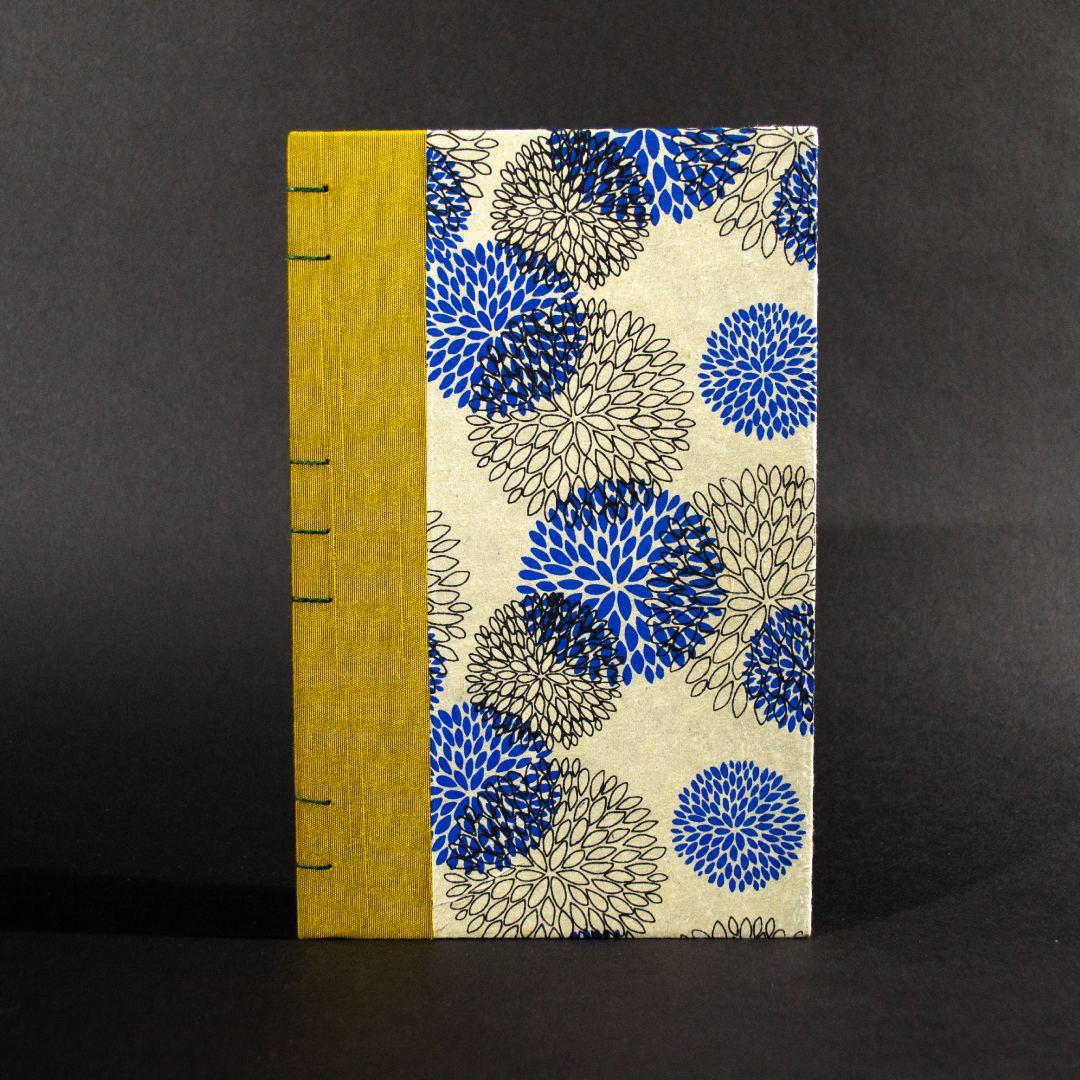 Front cover of blue floral lined quarto Coptic bound journal with gold bookcloth on the spine and and blue and black flowers on an ivory background