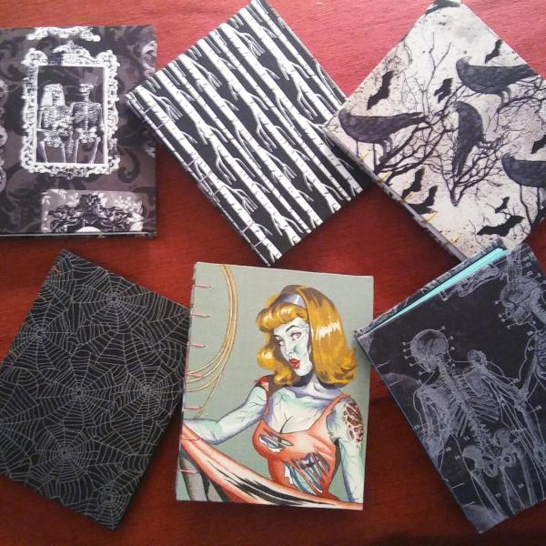 A photo of some recent Coptic bound books. From upper left: Victorian skulls, black and white trees, bats & ravens, cobwebs, zombie pinup girl, and x-ray skeleton.