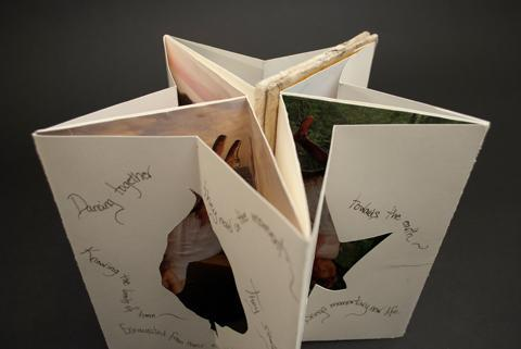 This photo is a front and top down view of two nested accordion structures that are arranged in a circle to form a star. The inside pages are covered in photos of dancers and the front has poetry surrounding cut out leaves. This structure is a Carousel book class example by Laurel Tree Bindery.