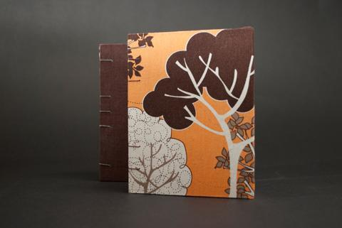 This photograph is two optic stitch books, one brown, and one with orange and brown trees. It's a promotional studio photo for the coptic duo class by Laurel Tree Bindery.