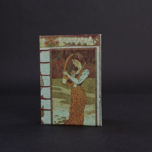 Art Nouveau Lady Coptic bound journal cover featuring a 3/4 shot of a lady in an orange dress holding a harp.