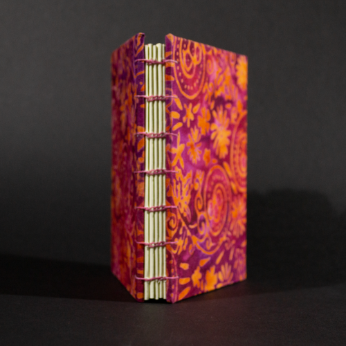 Spine of orange floral batik octavo Coptic book