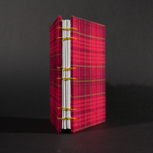 Spine view of red plaid octavo Coptic bound journal with inside white end pages and text pages