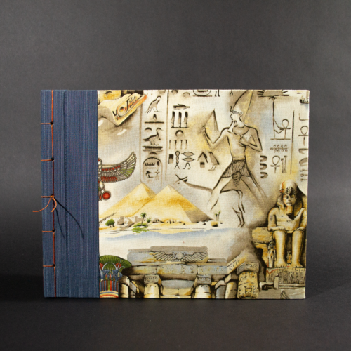 Front cover of stab bound Egyptian photo album showing the blue book cloth left side and a with Egyptian themed fabric featuring a pharaoh, pyramids, and hieroglyphics.
