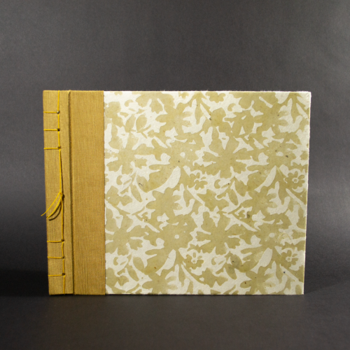 Stab bound floral photo album has gold book cloth on the left side and the paper has a waxed floral pattern