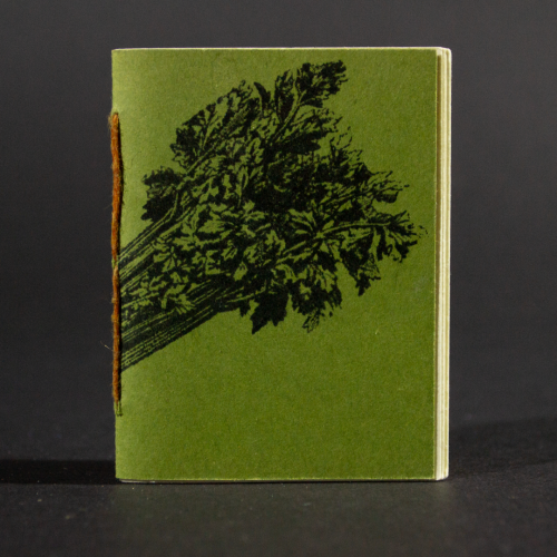 A celery stick wraps around the green front cover of this mini pamphlet book