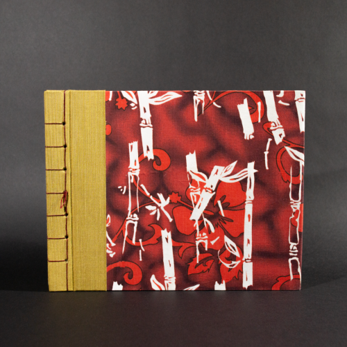 Stab bound Hawaiian photo album has gold book cloth on the left side and a Hawaiian floral pattern with bamboo and hibiscus
