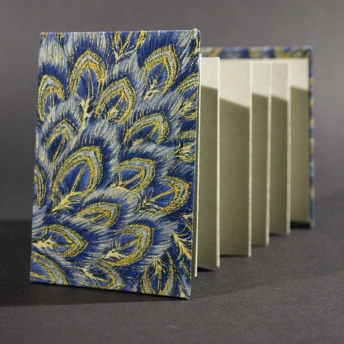 The front cover of the peacock medium accordion book has peacock feathers in blue and gold with heavy gray inside pages.