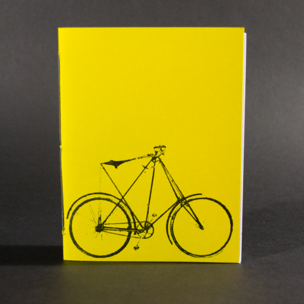 Pamphlet binding class sample of a bound book with a yellow cover and a bicycle in black on the cover.