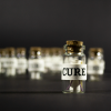 Cures product shot. A photo of a small glass bottle with a scroll inside. The outside is wrapped in paper and labelled cure.